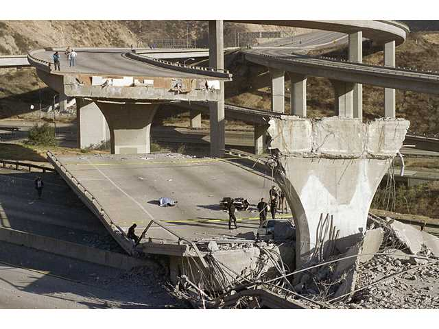 In this Jan. 17, 1994 file photo, the covered body of Los Angeles Police Officer Clarence Wayne Dean, 46, lies near his motorcycle, which plunged off the State Highway 14 overpass that collapsed onto Interstate 5, an interchange that is now named in his memory.
