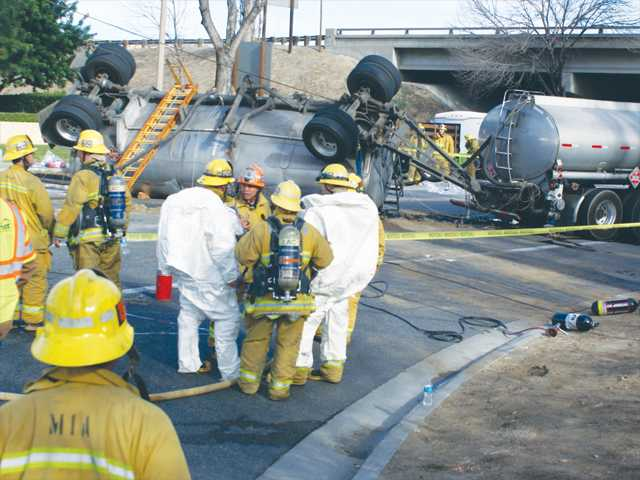 County firefighters from the Hazardous Materials Unit (in white) survey the scene after the spill as crews work to contain the spread of oil onto the road. Signal photo by Jim Holt.