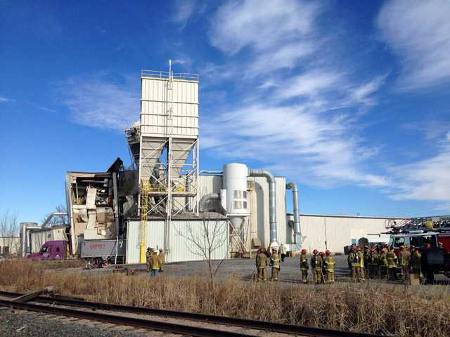 Firefighters stand outside the International Nutrition plant in Omaha, Neb., on Monday, where a fire and explosion took place.