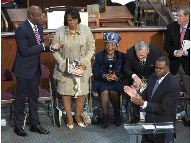 Bernice King, second from left, is honored by Atlanta mayor Kasim Reed, lower right, for her speech earlier during the Rev. Martin Luther King Jr. holiday commemorative service at Ebenezer Baptist Church Monday in Atlanta. Bernice King is the daughter of the late Dr. Martin Luther King Jr.