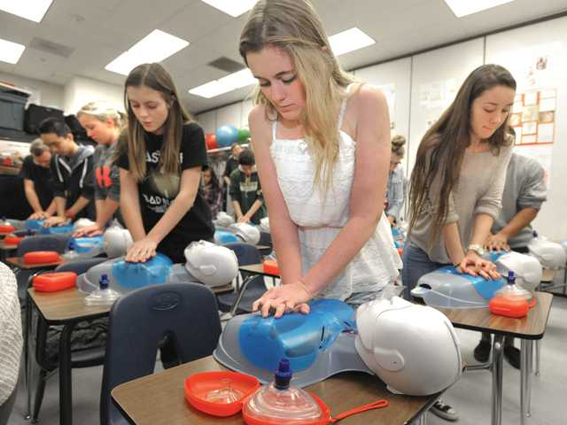Valencia students, from left, Elena Subbotin, Caley Mike and Kianna Galli practice chest compressions during an advanced heart training course in the Sports Medicine class at Valencia High School. Signal photo by Dan Watson.