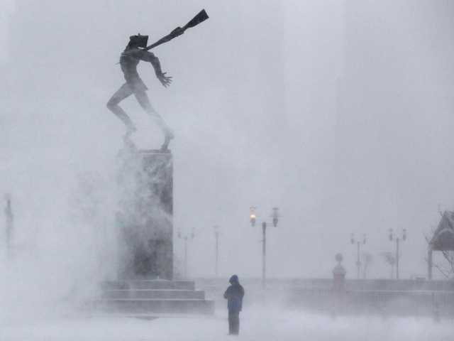 Wind picks up snow from the ground as a man waits to take a photograph of a statue dedicated to the victims of the 1940 Katyn massacre in Jersey City, N.J. on Tuesday.