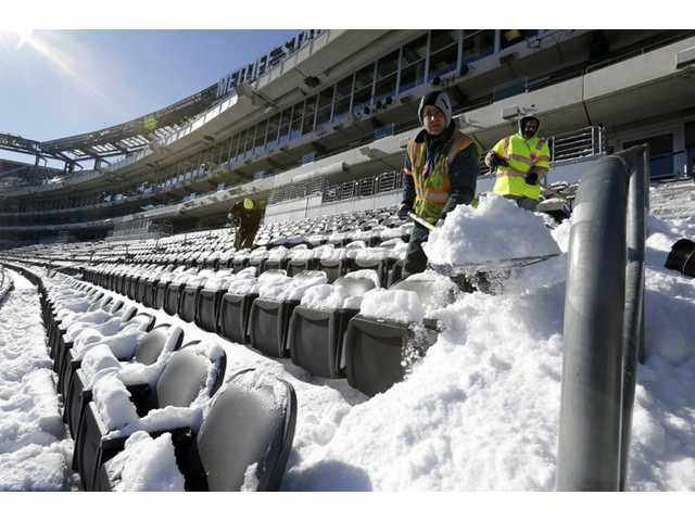 Workers shovel snow off the seating area at MetLife Stadium as crews removed snow ahead of Super Bowl XLVIII following a snow storm on Wednesday in East Rutherford, N.J.