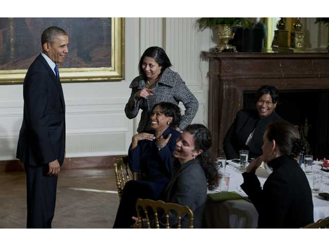 President Barack Obama laughs with women in the East Room of the White House in Washington on Wednesday as he leaves an event for the Council on Women and Girls, where he signed a memorandum creating a task force to respond to campus rapes.