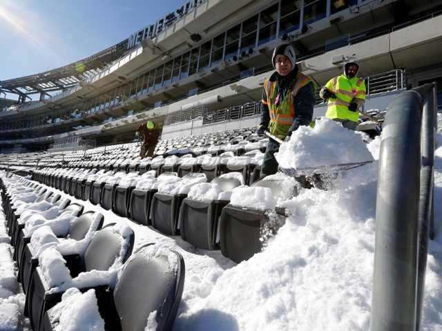 Workers shovel snow off the seating area at MetLife Stadium as crews removed snow ahead of Super Bowl XLVIII following a snow storm on Wednesday.