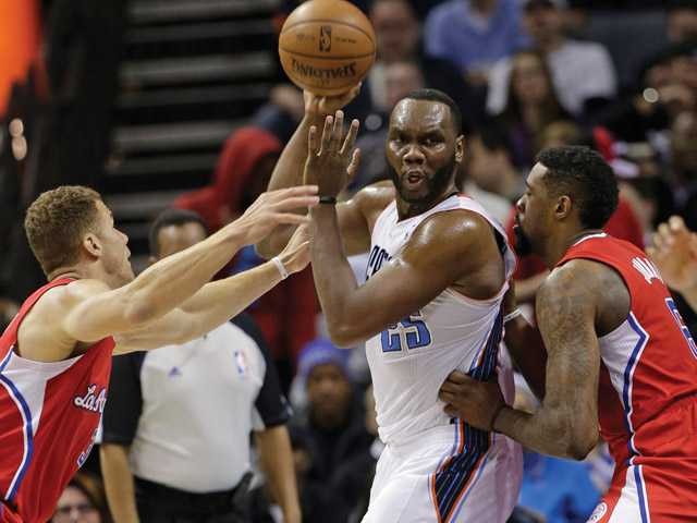 Charlotte Bobcats' Al Jefferson,center, looks to pas as he is trapped by Los Angeles Clippers' DeAndre Jordan, right, and Blake Griffin, left, during the second half of an NBA basketball game in Charlotte, N.C., Wednesday, Jan. 22, 2014. The Bobcats won 95-91.