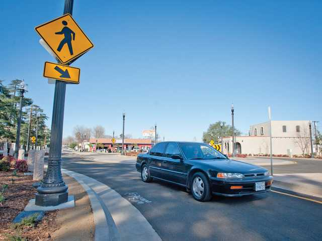 A driver loops around the newly finished roundabout in Newhall on Thursday. Signal photo by Charlie Kaijo.