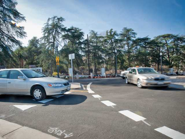 Drivers loops around the newly finished roundabout in Newhall in front of Hart Park on Thursday. City officials were on hand for a ribbon cutting ceremony before some vintage automobiles made the first trips in the traffic circle. Signal photo by Charlie Kaijo.