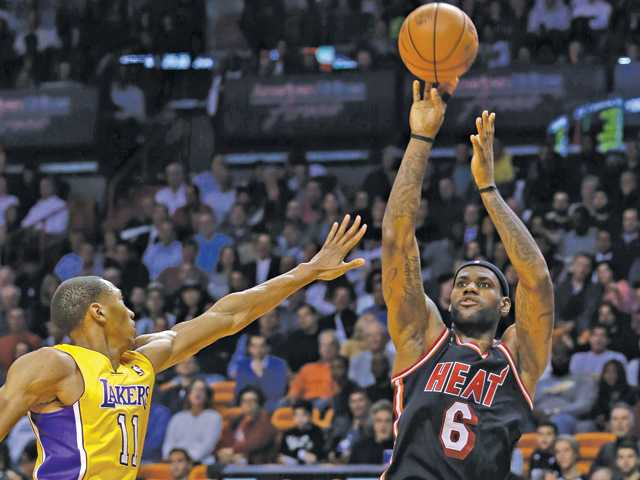 Miami Heat forward LeBron James (6) shoots for three points over Los Angeles Lakers forward Wesley Johnson (11) during the second quarter of an NBA basketball game in Miami, Thursday. The Heat won 109-102.