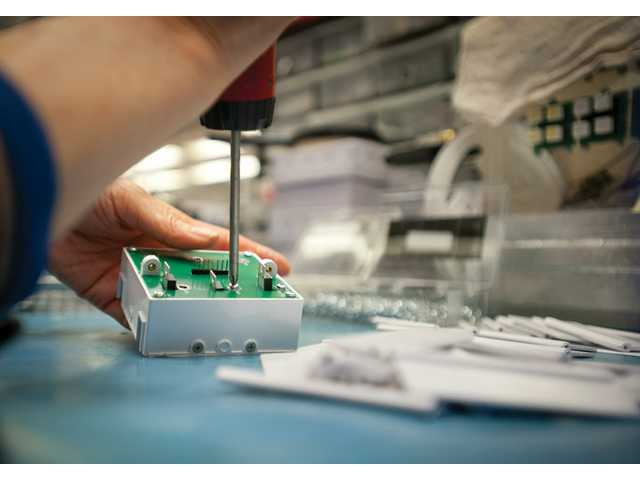 Tot Chittamai builds an LED alarm system at the Ronan Engineering factory.