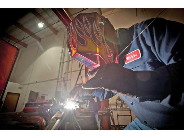 Fransisco Cortez welds a frame for a circuit board at the Ronan Engineering factory.