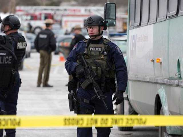 A heavily armed police officer walks on scene after a shooting at The Mall in Columbia on Saturday, Jan. 25, 2014 in Columbia, Md. Police say three people died in a shooting at the mall in suburban Baltimore, including the presumed gunman.