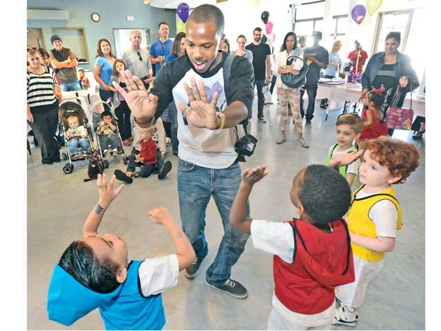 Instructor Marquis Wooten of Movement Inc Dance Center high-fives the youngsters who participated in a Hip-Hop dance demonstration at the preschool fair.
