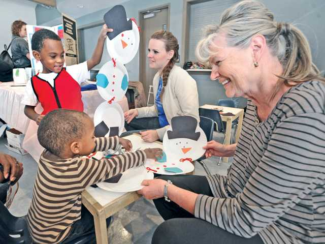 Rafiel Yoakum, left, and brother Jalil, 2, create snowmen from paper plates with assistance from Britney Smith, center, and Connie Luechtefeld at the Little Shepherd Preschool booth at the Preschool Fair held at Valencia United Methodist Church in Valencia on Saturday.