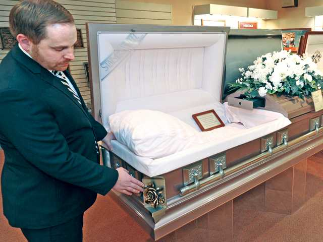 Mortuary Supervisor Steven Mahrle shows various choices for caskets, including wood or steel, in the main offices of Eternal Valley Memorial Park and Mortuary in Newhall on Tuesday.