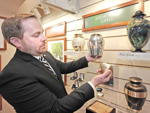 Mortuary Supervisor Steven Mahrle displays tree typle of crematory urns from left, mother of pearl, nickel plated brass and glass.