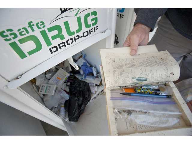 Detective Pat Murphy opens a hollowed-out book containing marijuana found in the safe drug drop-off box at the Santa Clarita Sheriff's Department on Thursday.