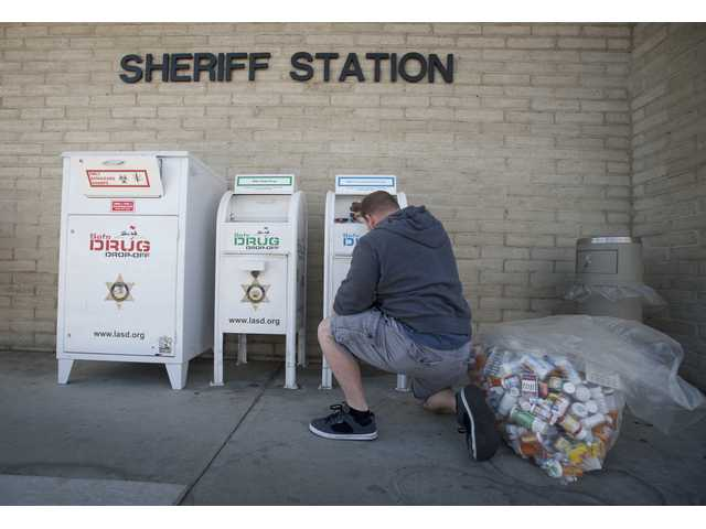 Murphy locks the prescription drug drop-off box after emptying its contents.