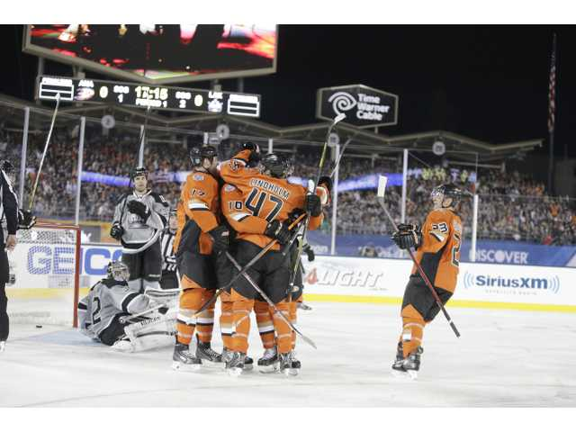 The Anaheim Ducks celebrate a goal by right wing Corey Perry during the first period Saturday's game at Dodger Stadium.
