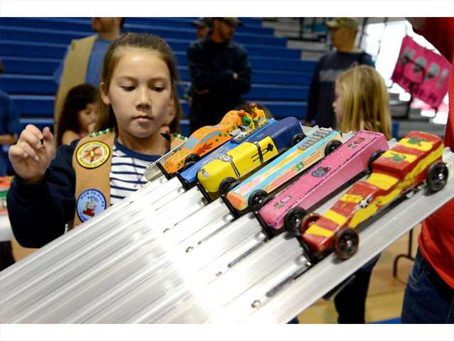 Amelia Haydamaek 8, hits the lever to release the wooden cars as they race down the track during Sunday's YMCA Pinewood Derby, held at the Saugus High School gym. Photo by Jayne Kamin-Oncea for The Signal.