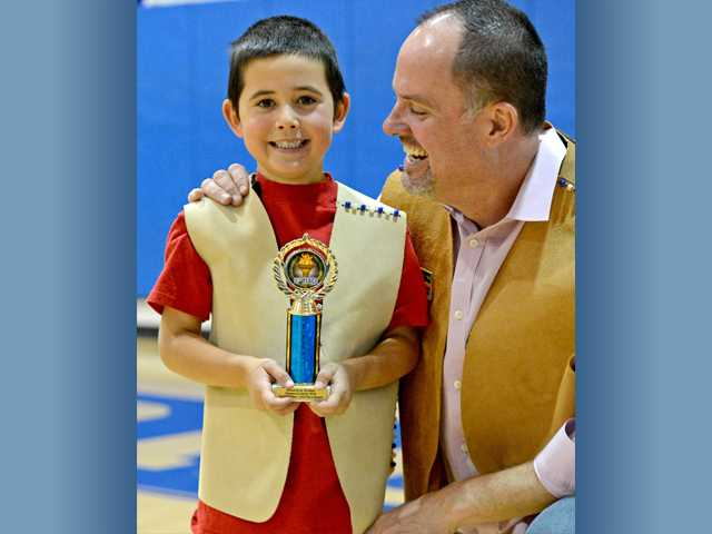 Harrison Crume, 5, proudly holds his trophy with his father, T.J. Crume, at his side at the end of the Pinewood Derby on Sunday. Photo by Jayne Kamin-Oncea for The Signal.