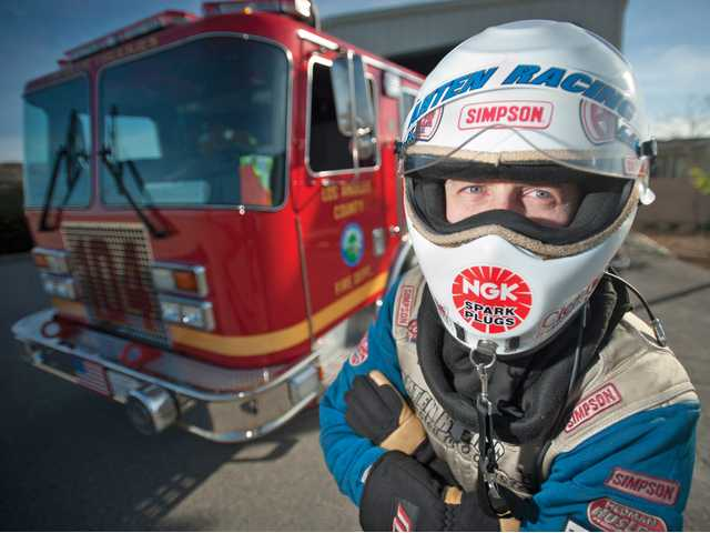 Capt. Johnny Ahten stands in front of the company fire engine at Fire Station No. 104, dressed in the outfit for his other calling: drag racing. Signal photo by Charlie Kaijo.