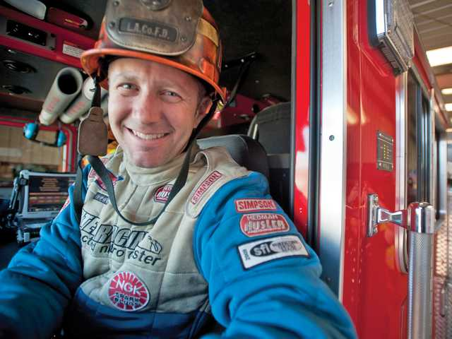 Capt. Johnny Ahten, who heads Fire Station No. 104 in Santa Clarita, sits in the company fire engine, in a mix of fire and drag racing gear.Signal photo by Charlie Kaijo.