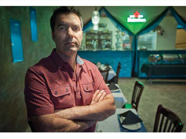 Homayoun Daryani, owner of the Persia Lounge in Newhall, poses for a portrait in his business on Thursday. Signal photo by Charlie Kaijo.