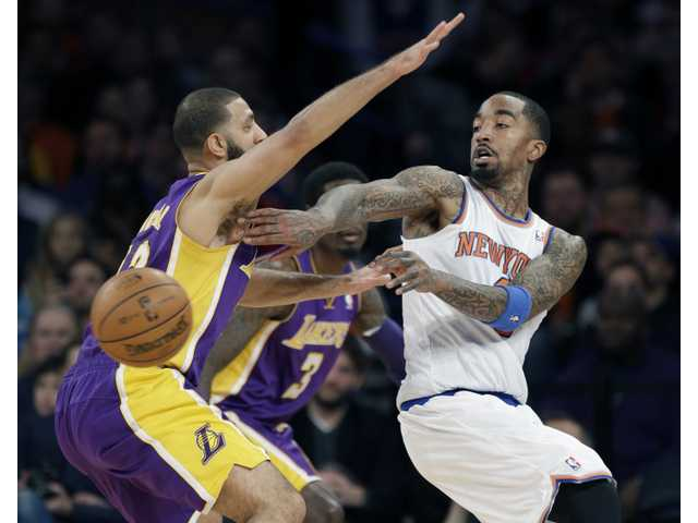 New York Knick J.R. Smith, right, passes around Laker Kendall Marshall during the second half of Sunday afternoon's game  in New York.