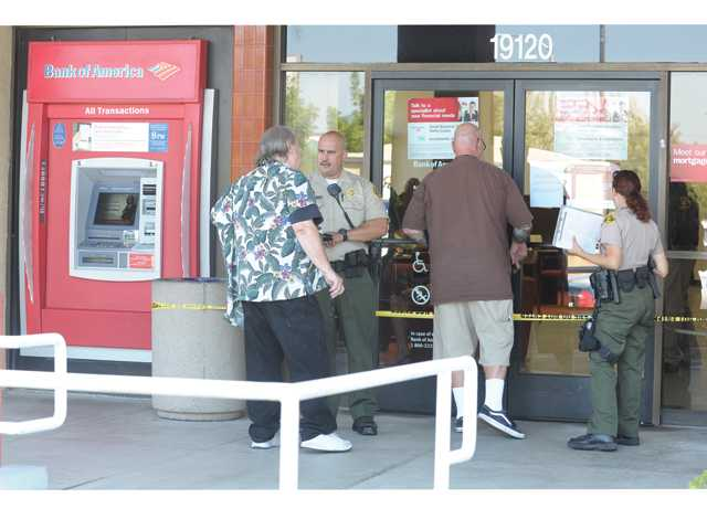 FILE: Sheriff's Deputies talk to customers after a robbery occurred at the Bank of America on Soledad Canyon Road in Canyon Country on September 12, 2012.