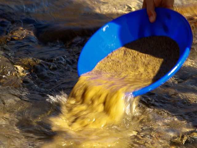 In this photo from Jan. 26, a prospector sifts for gold in the Bear River near Colfax.