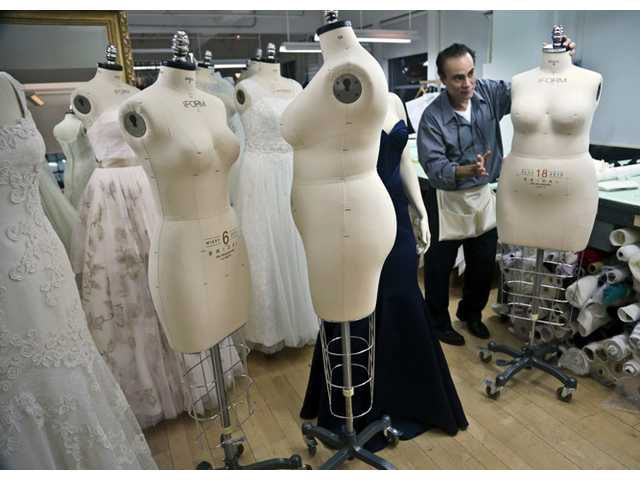 In this Dec. 17, 2013 photo, David's Bridal dressmaker Noel Belancourt, wheels a plus-size mannequin to his workstation in New York.