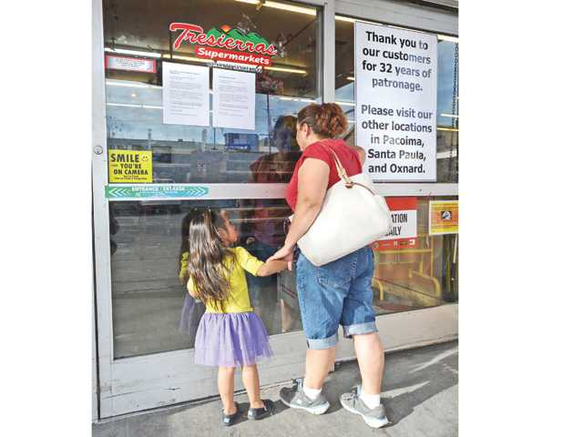 A sign posted on the window thanks customers for 32 years of patronage as Aracely Chandres, right, and her daughter Alejandra, 3, peer in the locked doors of the Tresierras Supermarket located on Main Street in Newhall on Tuesday. Signal photo by Dan Watson.