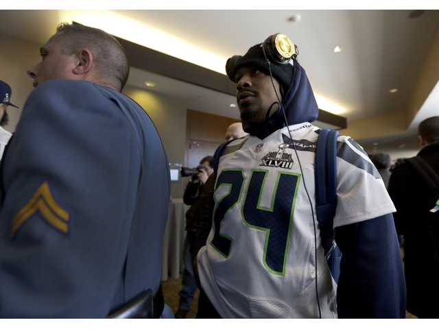 A police officer escorts Seattle Seahawks running back Marshawn Lynch, right, to a media session on Wednesday in Jersey City, N.J.