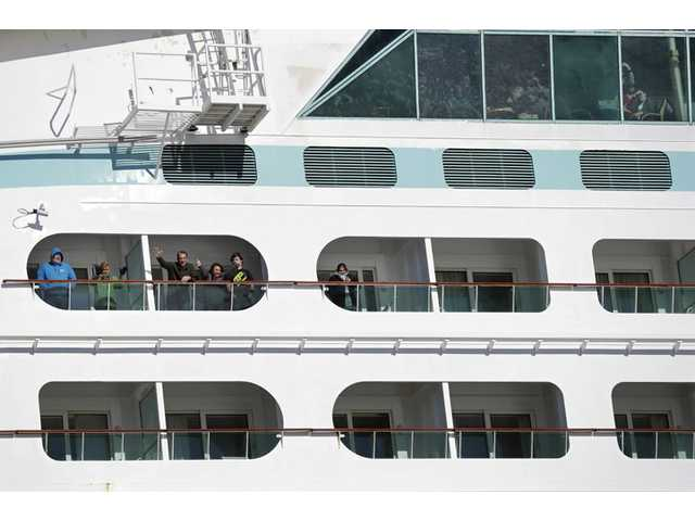 People look out from the Explorer of the Seas cruise ship as it docks at a berth Wednesday in Bayonne, N.J.