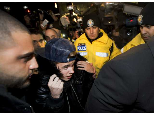Canadian musician Justin Bieber is swarmed by media and police officers as he turns himself in to city police for an expected assault charge in Toronto on Wednesday.