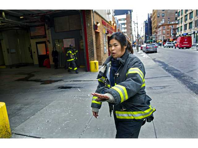 New York City firefighter Sarinya Srisakul holds back pedestrians as she awaits a firetruck to exit a Manhattan firehouse as she goes on an emergency call Tuesday in New York.