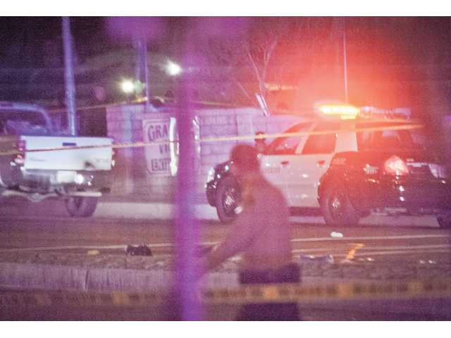 A sheriff's deputy walks past the male suspect lying next to the center divider on the corner of Soledad Canyon Road and Shangri-La Drive Thursday night in Canyon Country. Signal photo by Charlie Kaijo.