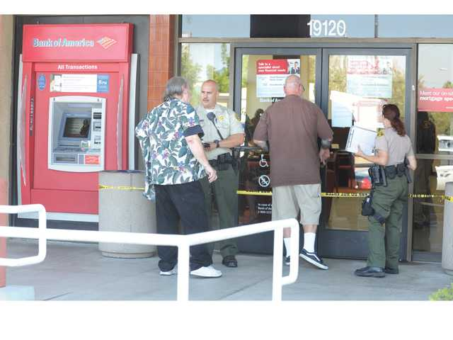Sheriff's deputies talk to customers after a robbery occurred at the Bank of America on Soledad Canyon Road in Canyon Country on Sept. 12, 2012.