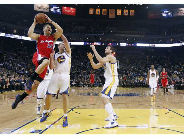 Los Angeles Clipper Blake Griffin, left, goes up for a shot next to Golden State Warriors players on Thursday in Oakland.