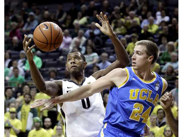 Oregon forward Mike Moser, left, and UCLA forward Travis Wear battle for a rebound in Eugene, Ore. on Thursday.