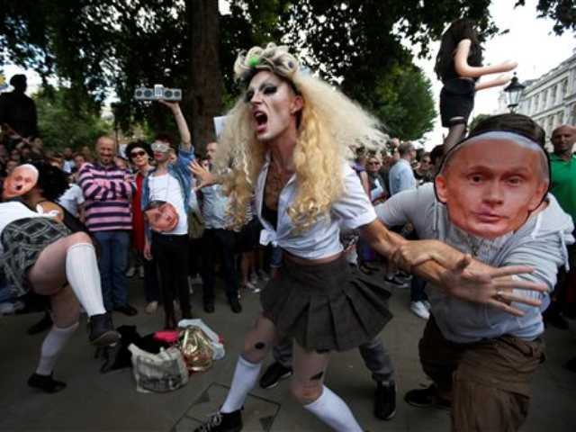 "In this Saturday, Aug. 10, 2013 file photo, demonstrators stage a theatrical play where gays are grabbed by others wearing masks of Russian President Vladimir Putin, during a protest against Russia's new anti-gay law banning ""propaganda of nontraditional sexual relations"" in central London."