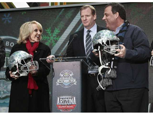 NFL Commissioner Roger Goodell, center, stands between Arizona Gov. Jan Brewer, left, and New Jersey Gov. Chris Christie, right, showoff souvenir football helmets after a ceremony to pass official hosting duties of next year's Super Bowl to Arizona, Saturday Feb. 1, 2014 in New York.