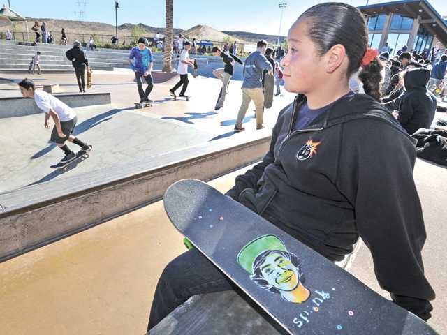 Amber Arreseigor, 13, sits with her skateboard decorated with a caricature of Albert Castro at the Albert Castro Memorial Skate Jam event held at the city of Santa Clarita Skate Park on Saturday.