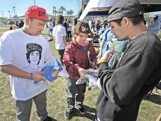 Event organizers Cody Le and Joseph Aguilar, right, hand out T-shirts to attendees.