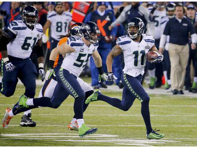 Seahawks wide receiver Percy Harvin (11) returns a kickoff for a touchdown against the Denver Broncos in the Super Bowl in East Rutherford, N.J.
