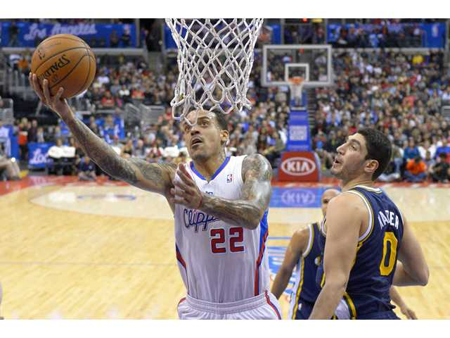 Los Angeles Clippers forward Matt Barnes, left, puts up a shot as Utah Jazz center Enes Kanter defends on Saturday in Los Angeles.