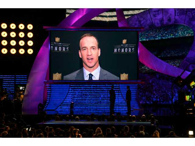 Denver Broncos quarterback Peyton Manning appears on screen to accept the award for AP MVP on Saturday in New York.