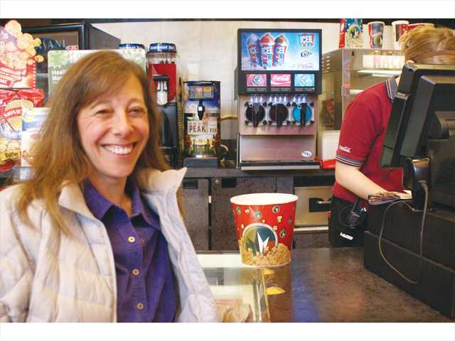 Tracy Bagatelle buys popcorn at the Edwards Cinema Santa Clarita movie complex on Super Bowl Sunday.  She and Bill Guthrie figured there would be fewer people at the theater. They were right. Photo by Jim Holt.