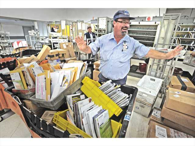 U.S. Post Office Letter carrier Mike Andrews reacts to his coworkers at the Valencia branch of the U.S. Post Office on Thursday as they kid him about his new-found fame as a singing letter carrier in a recent  USPS national ad campaign. Signal photo by Dan Watson.